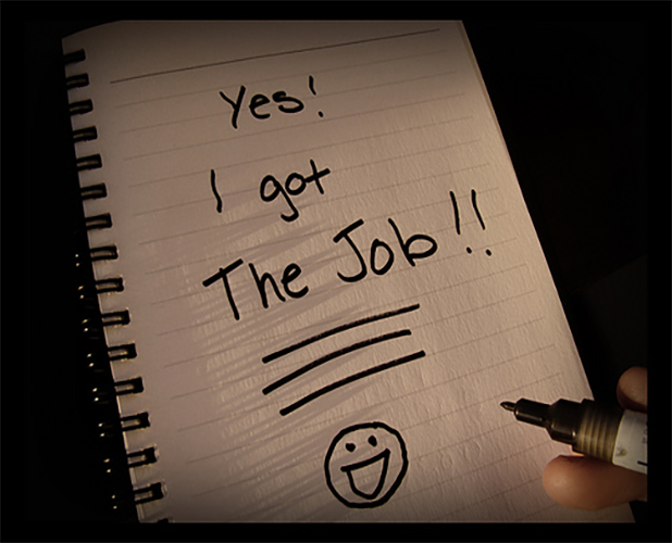 "Person writing ""yes I got the job! on notebook paper with black marker"